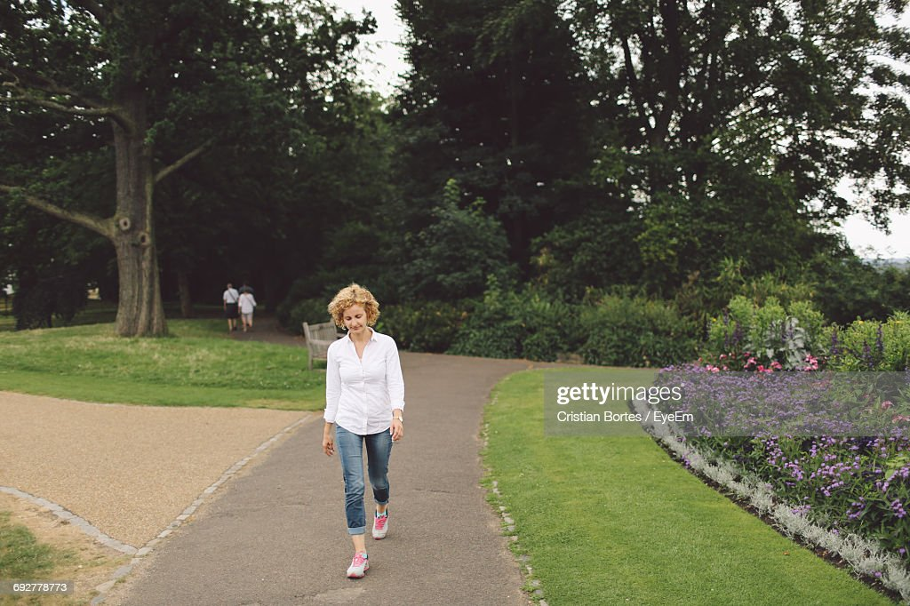 Full Length Of Woman Walking On Footpath In Park : Stock Photo