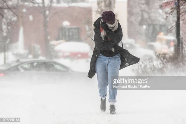 full length of woman walking on road during winter - winter weather stock photos and pictures