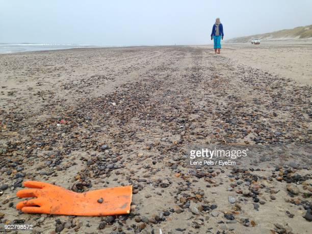 full length of woman walking on sand at beach - lene pels stockfoto's en -beelden