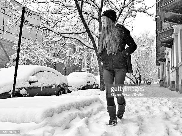 Full Length Of Woman Walking On Snow Covered Sidewalk In City