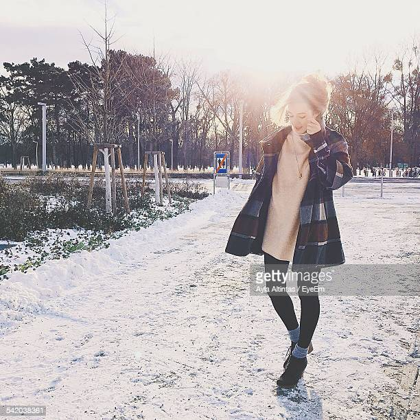 Full Length Of Woman Walking On Snow Covered Street During Winter