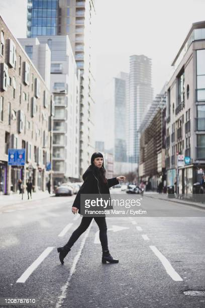 full length of woman walking on street against buildings in city - side view stock pictures, royalty-free photos & images
