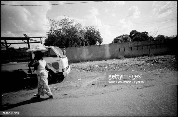 full length of woman walking on street by vehicle - ouagadougou stock pictures, royalty-free photos & images