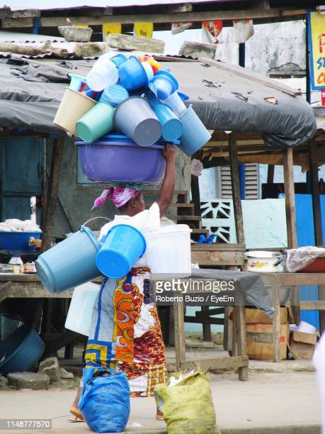 full length of woman walking while carrying plastic containers - femme ivoirienne photos et images de collection