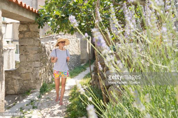 full length of woman wearing hat walking by plants - croatia stock pictures, royalty-free photos & images