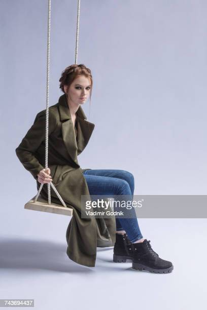 Full length of woman wearing long coat sitting on swing against purple background