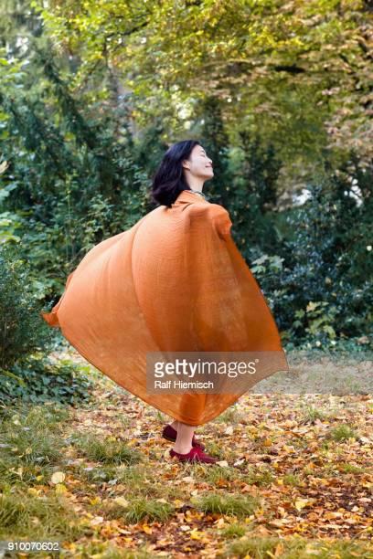 Full length of woman wearing orange scarf dancing against trees at park