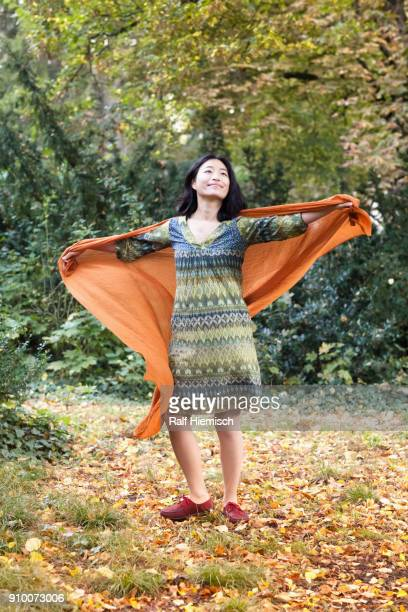 Full length of woman wearing orange scarf standing with arms outstretched at park during autumn