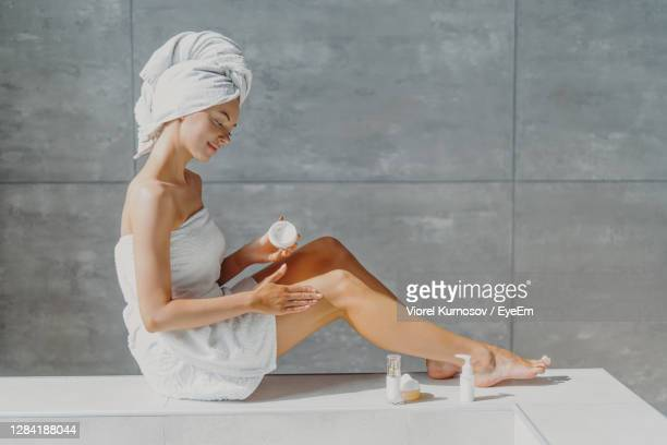full length of woman wearing towel applying moisturizer in bathroom - body care stock pictures, royalty-free photos & images