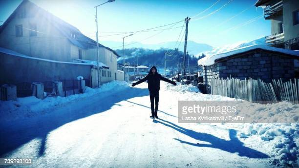 Full Length Of Woman With Arms Outstretched Standing On Snow Covered Street In Town