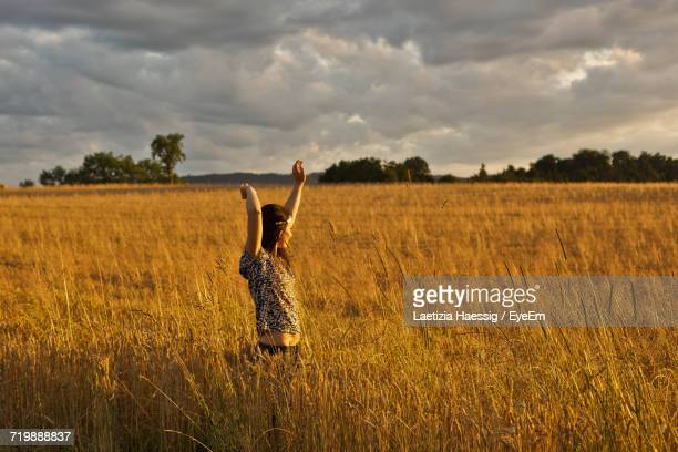 Full Length Of Woman With Arms Raised In Field