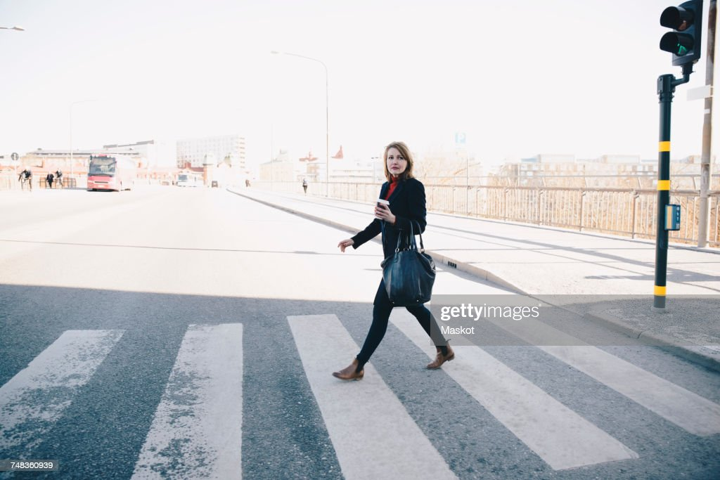 Full length of woman with bag walking on zebra crossing in city against clear sky during sunny day : Stock Photo