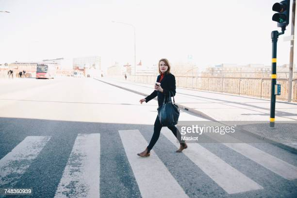 full length of woman with bag walking on zebra crossing in city against clear sky during sunny day - pedestrian crossing stock photos and pictures