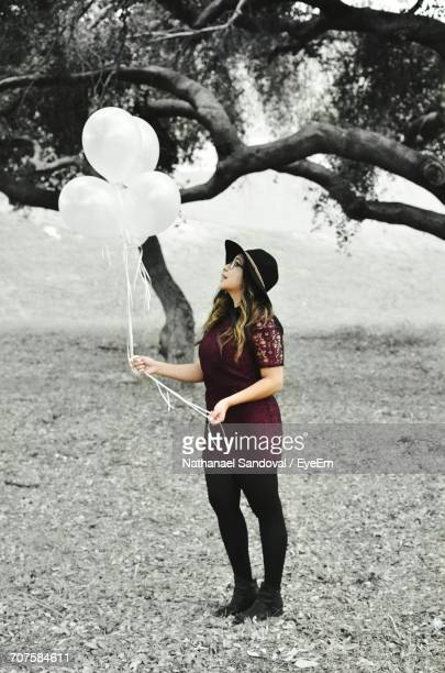 Full Length Of Woman With Balloons Standing In Park