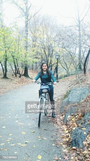 full length of woman with bicycle on road - laura belli foto e immagini stock