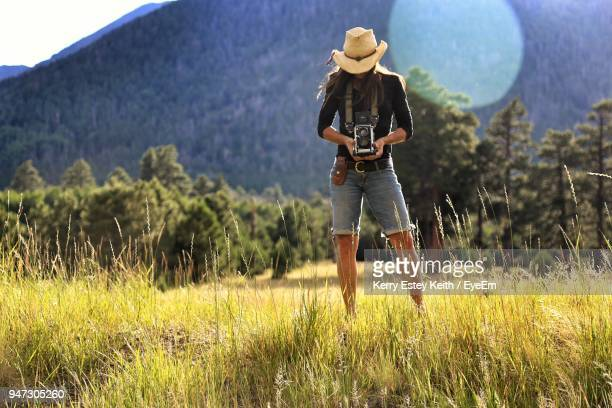 full length of woman with camera standing on field against mountains - kerry estey keith stock photos and pictures