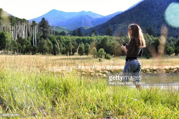 full length of woman with coffee mug standing on field against mountains - kerry estey keith stock photos and pictures