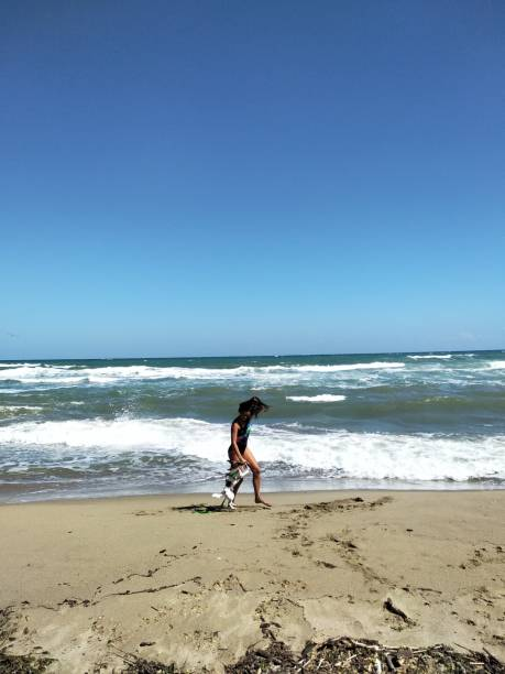 Full Length Of Woman With Dog On Shore At Beach Against Clear Blue Sky