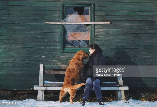 Full Length Of Woman With Dog Sitting On Bench Outside House During Winter