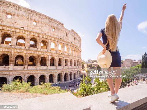 full length of woman with hand raised at coliseum - old ruin stock pictures, royalty-free photos & images