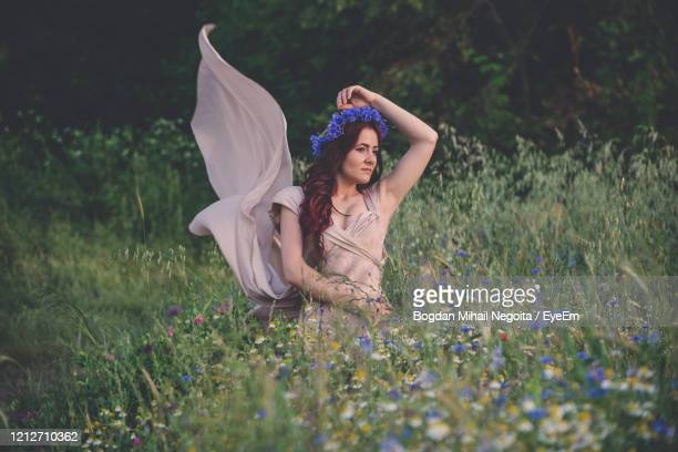 full length of woman with pink flowers on field - bogdan negoita stock pictures, royalty-free photos & images