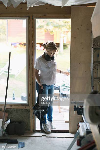 Full length of woman with tool belt entering in house being renovated