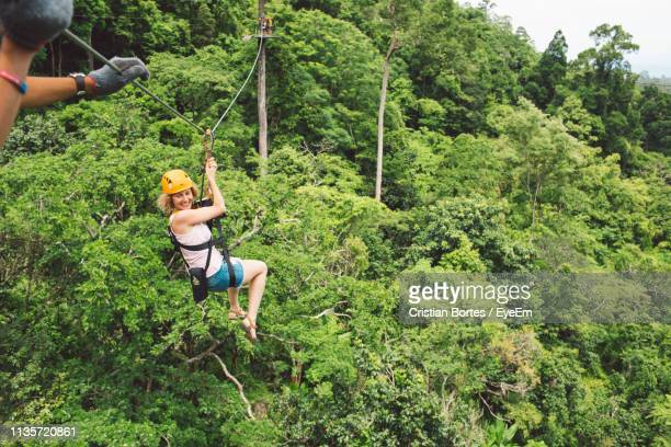 full length of woman zip lining at forest - bortes stock pictures, royalty-free photos & images