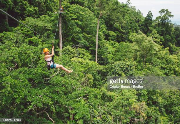 Full Length Of Woman Ziplining In Forest