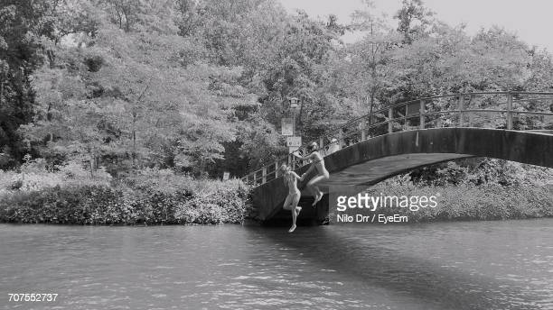 Full Length Of Women In Bikini Jumping Into River From Arch Bridge