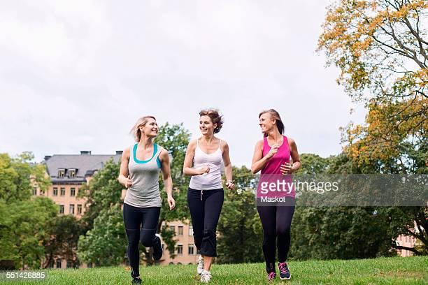 Full length of women jogging at park against sky