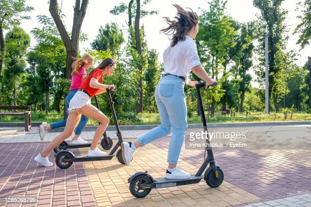 full length of women riding push scooter on the street - electric scooter stock pictures, royalty-free photos & images