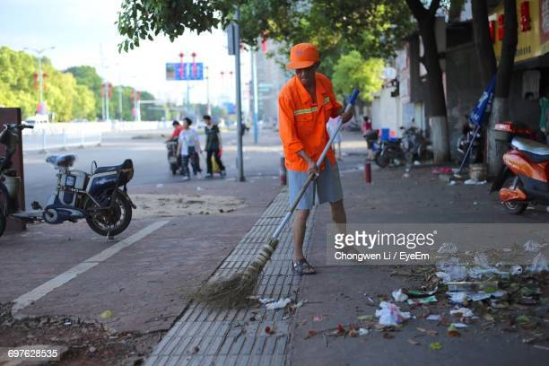 full length of worker sweeping footpath - street sweeper stock pictures, royalty-free photos & images