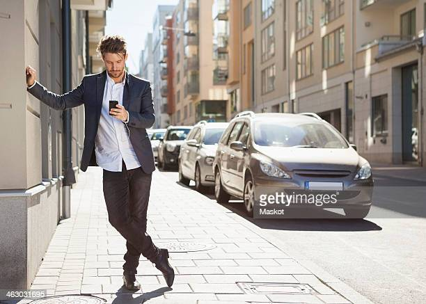 Full length of young businessman using mobile phone on sidewalk