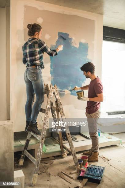 Full length of young couple painting their walls during home renovation process.