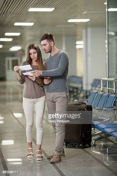 Full length of young couple reading tickets at airport