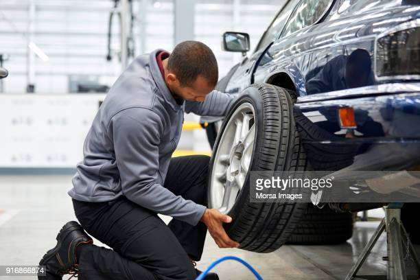 full length of young engineer adjusting car tire - vintage auto repair stock pictures, royalty-free photos & images