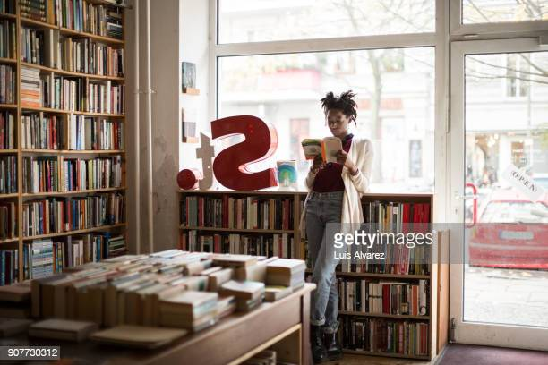 full length of young female customer reading book - book store stock photos and pictures