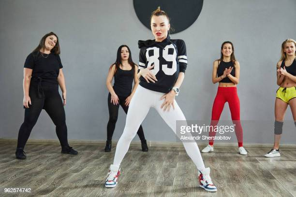 Full length of young friends standing on floor against wall at studio