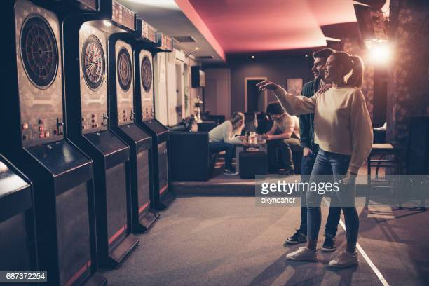 Full length of young happy couple playing darts in a bar.