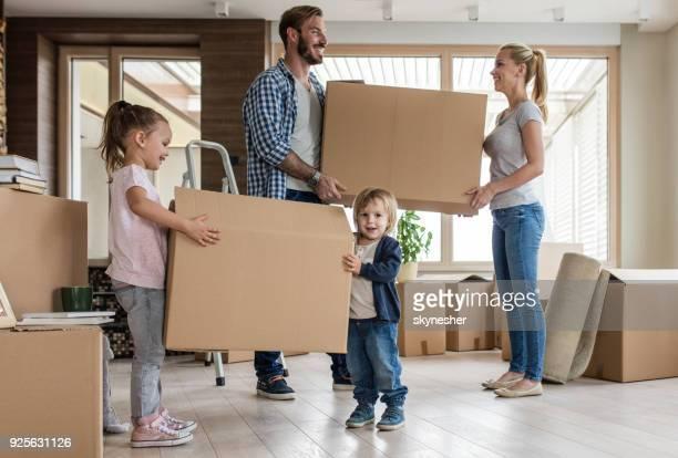 Gesamte Länge der junge glückliche Familie Einzug in ein neues Haus.