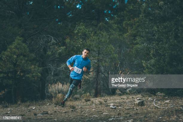 full length of young male athlete running in forest during marathon - marathon stock pictures, royalty-free photos & images