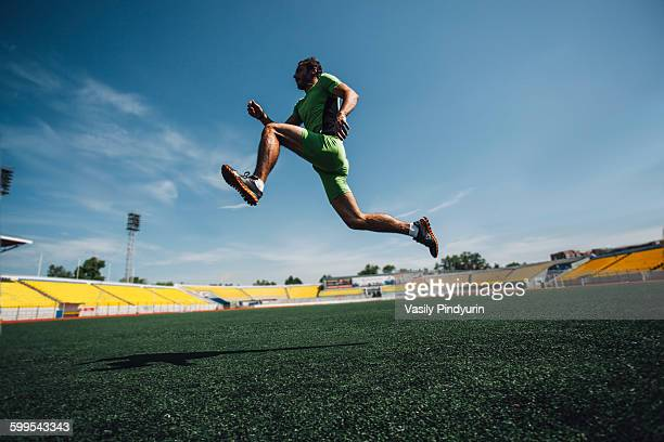 Full length of young male athlete running in stadium during training