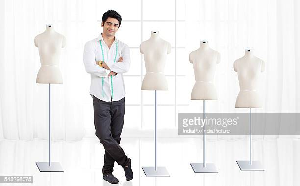 Full length of young male fashion designer standing by mannequin at studio