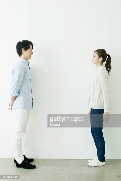 full length of young man and woman smiling face to face - 横からの視点 ストックフォトと画像