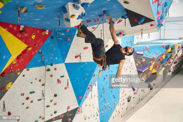 若い男がクライミングのジムで壁の全長 - クライミングウォール ストックフォトと画像