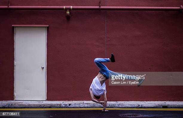 full length of young man doing cartwheel by maroon building - cartwheel stock pictures, royalty-free photos & images