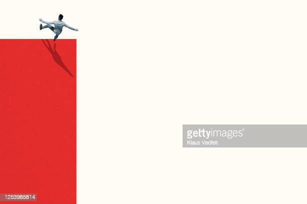 full length of young man falling from vibrant red wall - at the edge of stock pictures, royalty-free photos & images