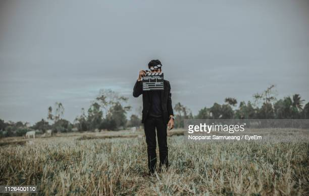full length of young man holding film slate on field - clapboard stock pictures, royalty-free photos & images
