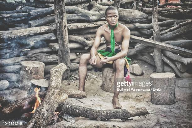 Full Length Of Young Man In Traditional Clothes Sitting On Log