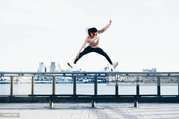 full length of young man jumping against clear sky - 足を開く ストックフォトと画像